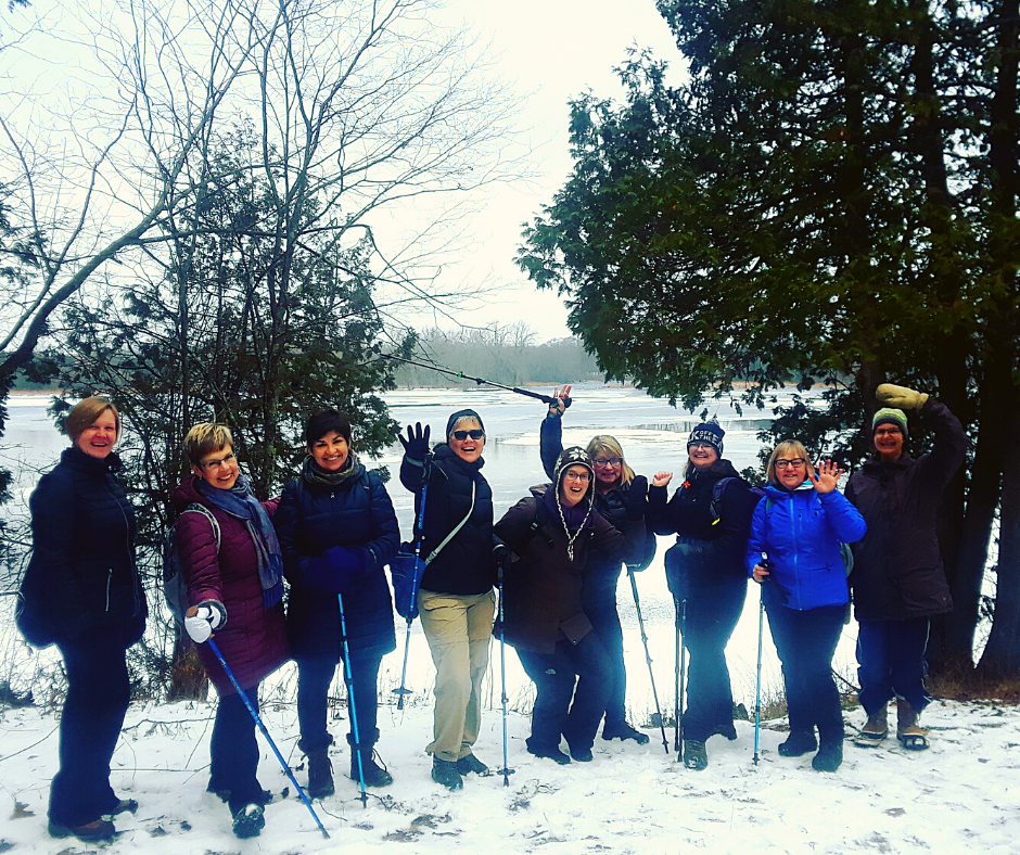 A group of smiling people standing in the snow