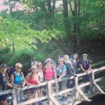 A smiling group of hikers posing on a wooden bridge